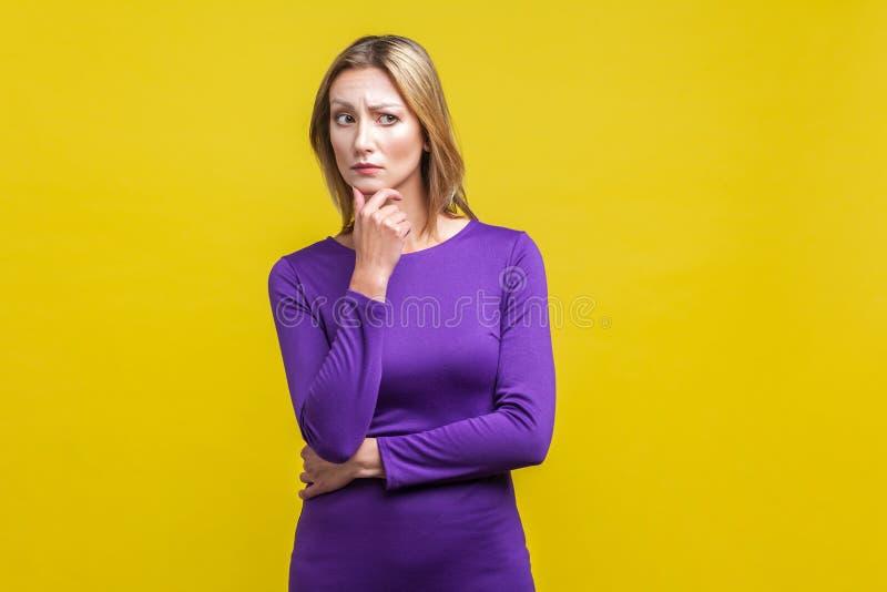Retrato de uma mulher confusa segurando o queixo enquanto pensava intensamente sobre fundo amarelo imagens de stock royalty free