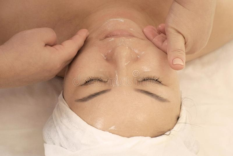 Retrato de uma mulher da aparência asiática que recebe uma massagem do bem-estar da cara Uma mulher com olhos fechados encontra-s fotografia de stock royalty free