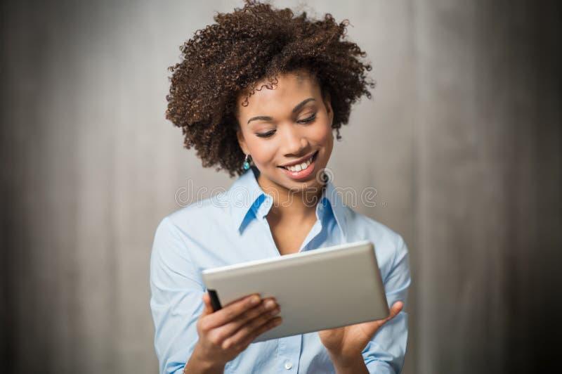 Mulher de negócios que usa a tabuleta de Digitas