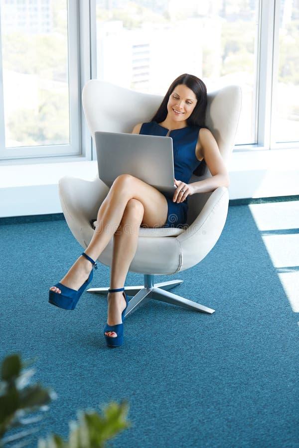 Retrato de uma mulher de negócio nova que usa o portátil no escritório Busin foto de stock