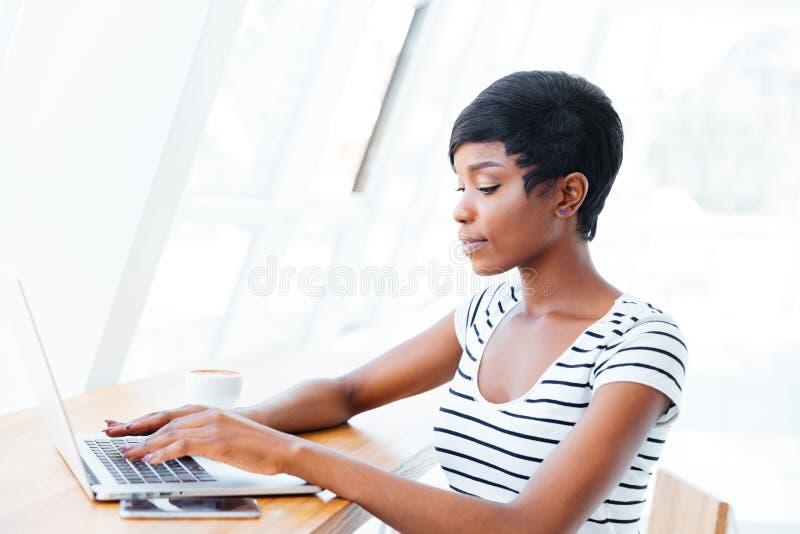 Retrato de uma mulher de negócios africana de sorriso ocasional que usa o laptop foto de stock