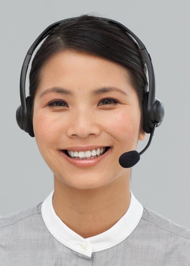 Retrato de uma mulher de negócios asiática com auriculares sobre imagens de stock