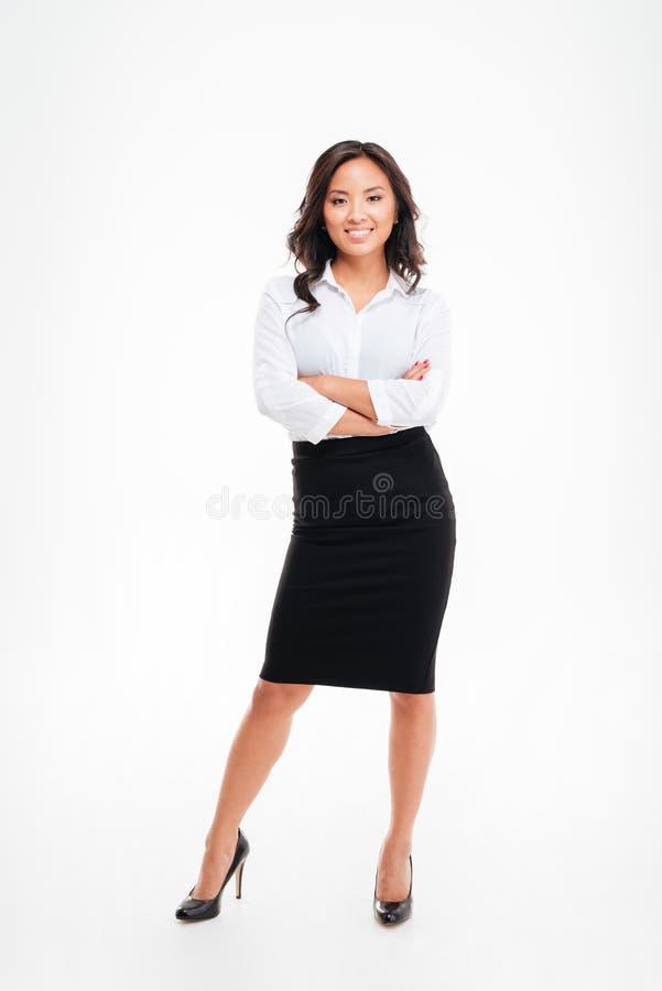 Retrato de uma mulher de negócios asiática de sorriso que está com os braços dobrados fotos de stock royalty free