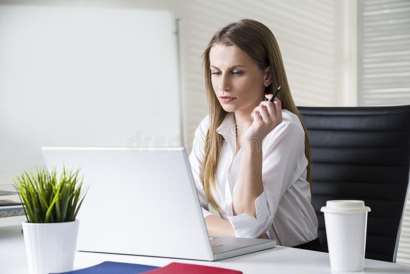 Retrato de uma mulher de negócios concentrada e bonita que veste uma blusa branca e que olha sua tela do portátil imagem de stock royalty free