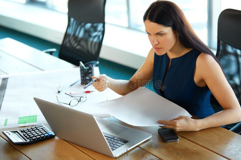 Retrato de uma mulher de negócios confusa que trabalhe com papéis dentro imagens de stock