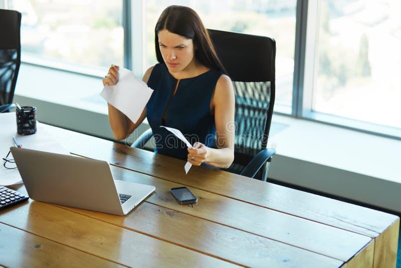 Retrato de uma mulher de negócios confusa que trabalhe com papéis dentro foto de stock royalty free
