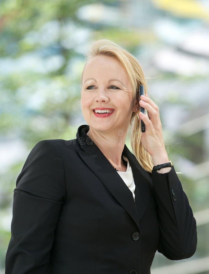Retrato de uma mulher de negócios madura que fala no telemóvel fotografia de stock royalty free