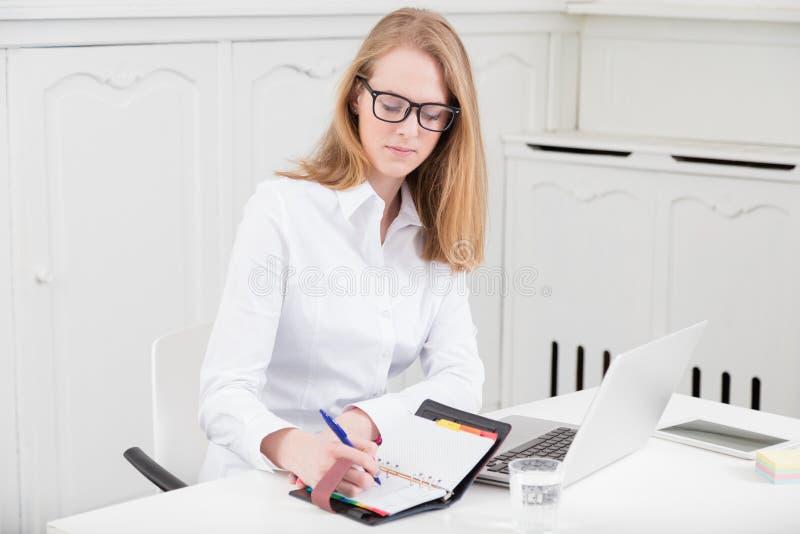 Retrato de uma mulher de negócios nova que toma notas na mesa foto de stock