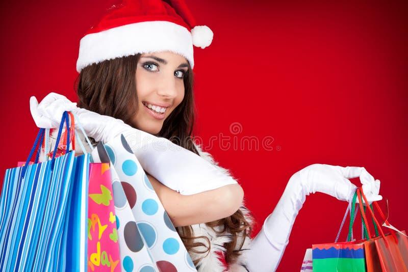 Retrato de uma mulher de Santa com sacos de compra fotografia de stock