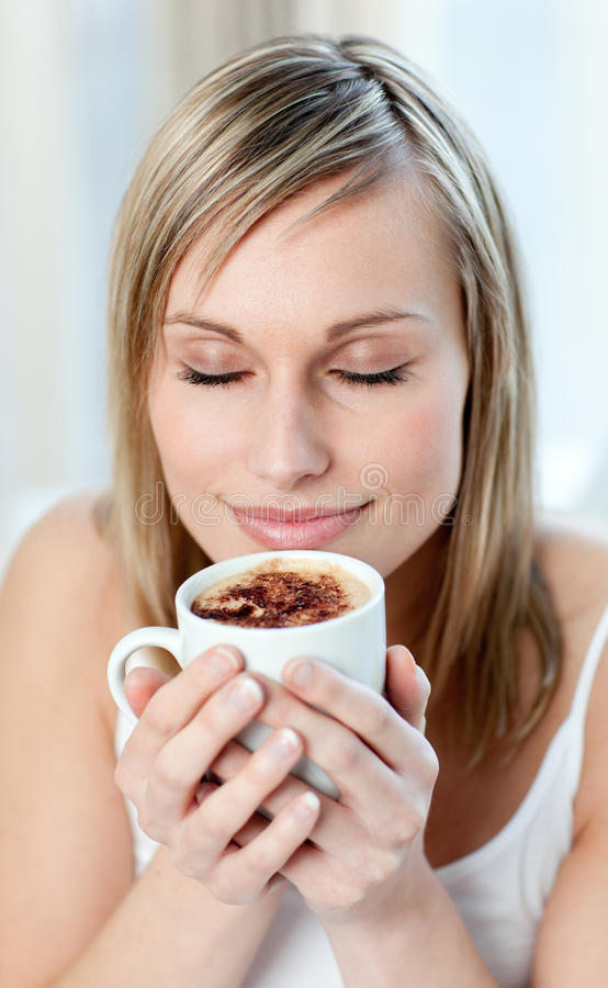 Retrato de uma mulher deleitada que bebe um café imagens de stock