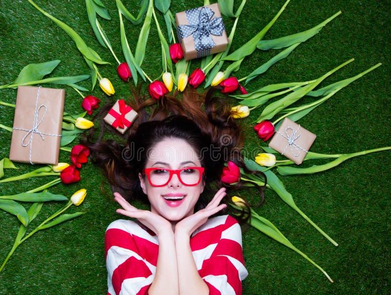 Retrato de uma mulher denominada nova do ruivo com tulipas ao redor e fotos de stock