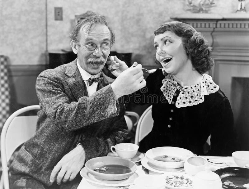 Retrato de uma mulher e de uma sopa de alimentação do homem entre si em uma tabela (todas as pessoas descritas não são nenhum da  fotografia de stock