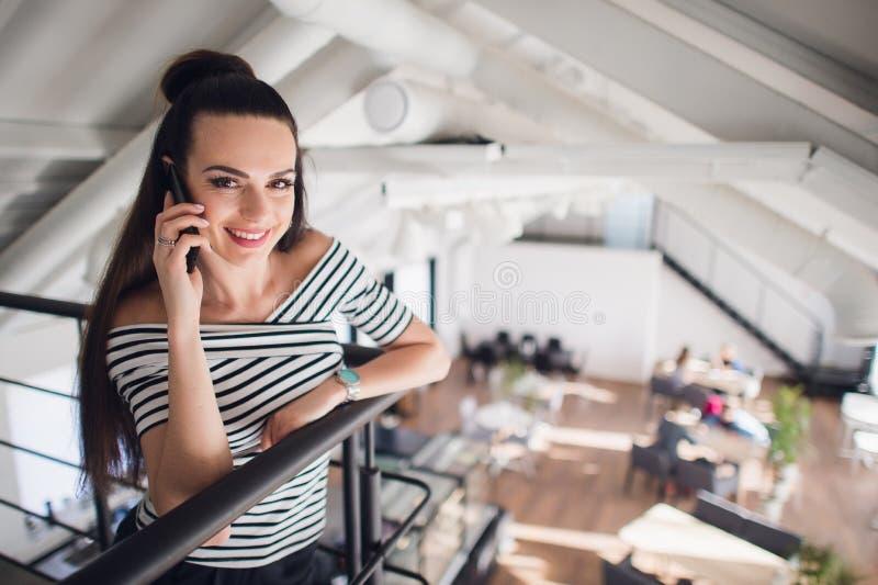 Retrato de uma mulher em um café que inclina-se contra os trilhos e que fala em seu telefone Fêmea adulta bonita que sorri e foto de stock royalty free