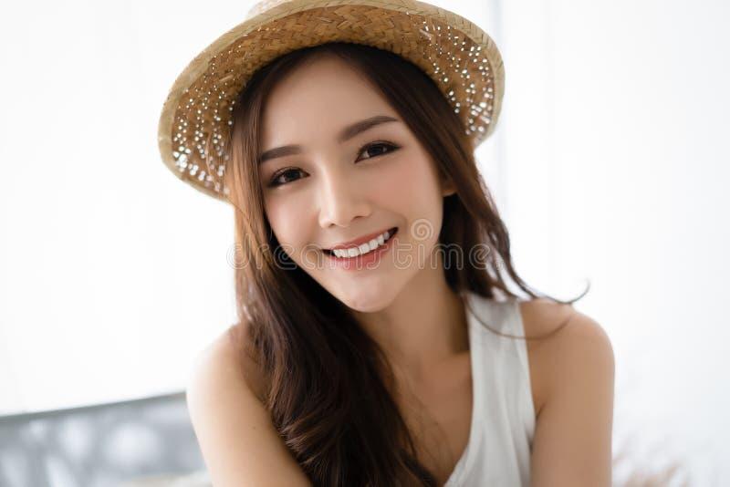 Retrato de uma mulher em um chapéu, retrato do close up de uma fêmea agradável no chapéu de palha do verão e de olhar a câmera Es foto de stock royalty free