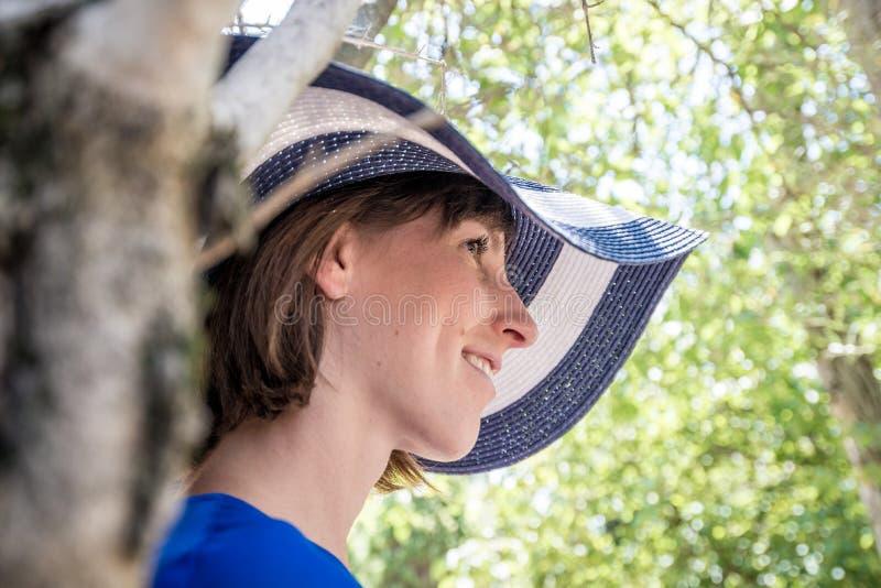 Retrato de uma mulher em um chapéu do sol que está de inclinação contra uma árvore fotos de stock