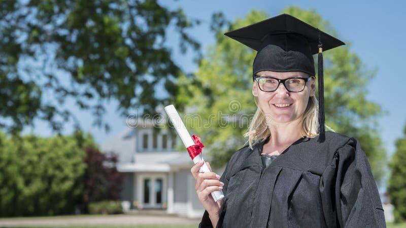 Retrato de uma mulher em um envoltório e em um tampão da graduação, guardando um diploma em sua mão na perspectiva de sua casa fotografia de stock royalty free