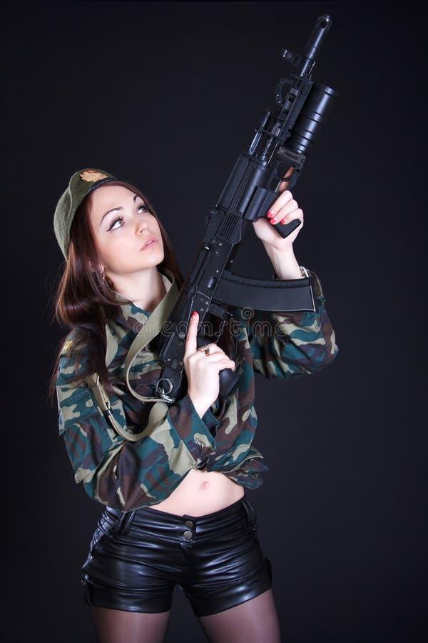 Retrato de uma mulher em um uniforme militar com uma espingarda de assalto imagens de stock