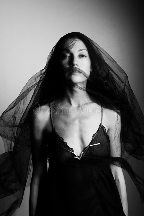 Retrato de uma mulher em um véu e em um roupa interior pretos fotos de stock