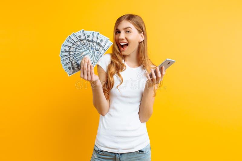 Retrato de uma mulher entusiasmado que mostra contas de dinheiro e que mantém o telefone celular isolado no fundo amarelo imagem de stock