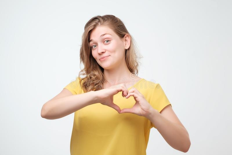 Retrato de uma mulher europeia nova de sorriso que mostra o gesto do coração com duas mãos e que olha a câmera imagem de stock