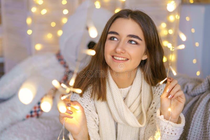 Retrato de uma mulher feliz com as festões em antecipação aos feriados do ano novo imagem de stock royalty free