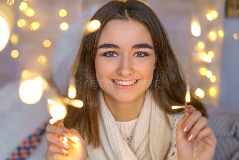 Retrato de uma mulher feliz com as festões em antecipação aos feriados do ano novo fotos de stock