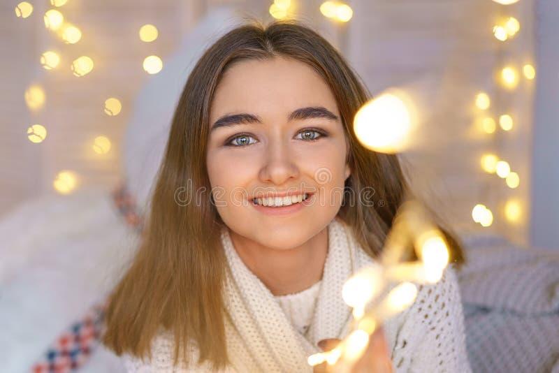 Retrato de uma mulher feliz com as festões em antecipação aos feriados do ano novo imagem de stock