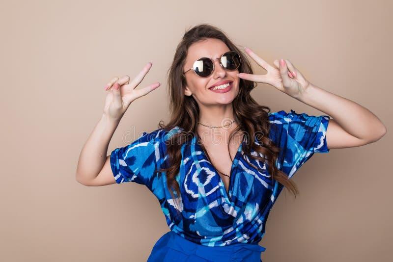 Retrato de uma mulher feliz de sorriso do playfull nos óculos de sol que mostram o sinal da vitória e que olham a câmera isolada  fotografia de stock royalty free