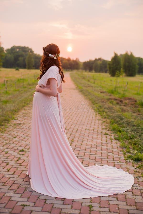 Retrato de uma mulher gravida feliz em um parque no nascer do sol com uma luz morna da parte traseira do rosa no fundo foto de stock