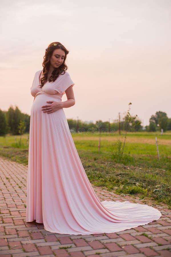 Retrato de uma mulher gravida feliz em um parque no nascer do sol com uma luz morna da parte traseira do rosa no fundo imagens de stock