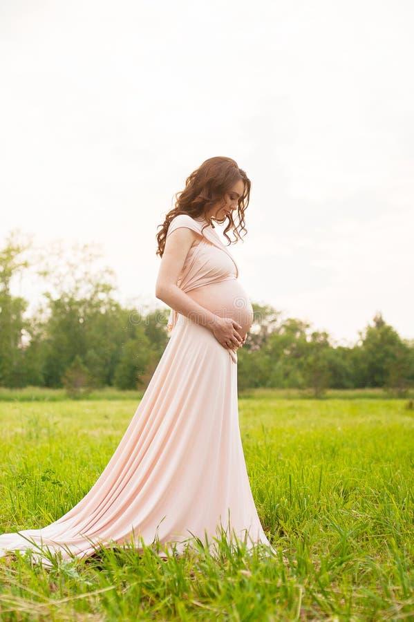 Retrato de uma mulher gravida feliz que olha sua barriga em um parque no nascer do sol com uma luz traseira morna no fundo fotos de stock