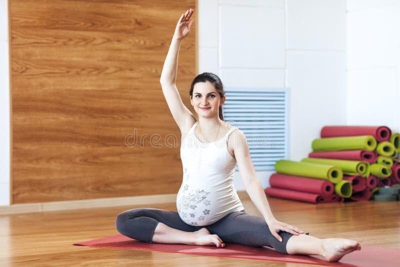 Retrato de uma mulher gravida nova bonita que faz exercícios Dar certo, ioga e aptidão, conceito da gravidez imagem de stock