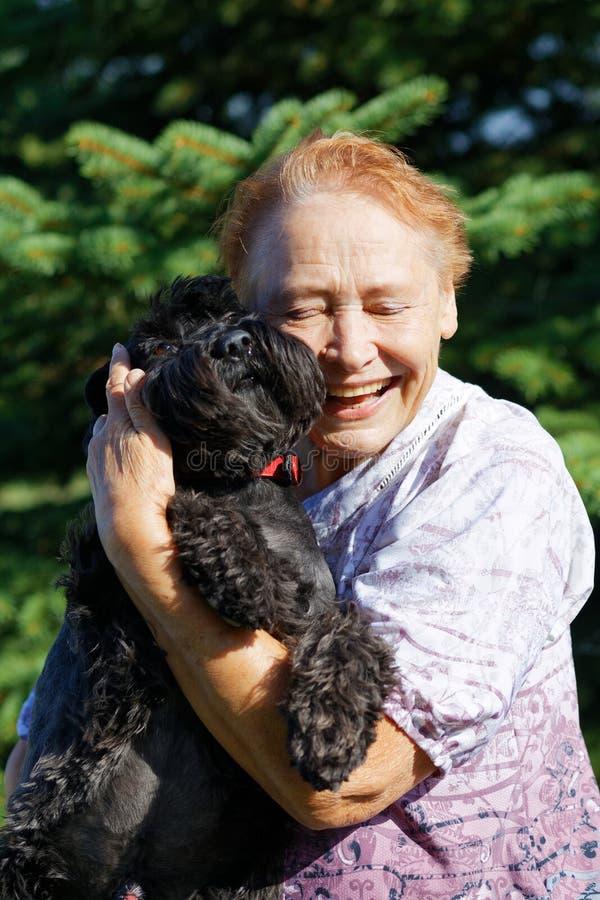 Retrato de uma mulher idosa que abraça o cão preto imagens de stock
