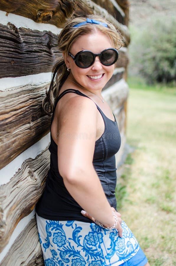 Retrato de uma mulher loura bonita que está ao lado de uma construção de madeira imagens de stock