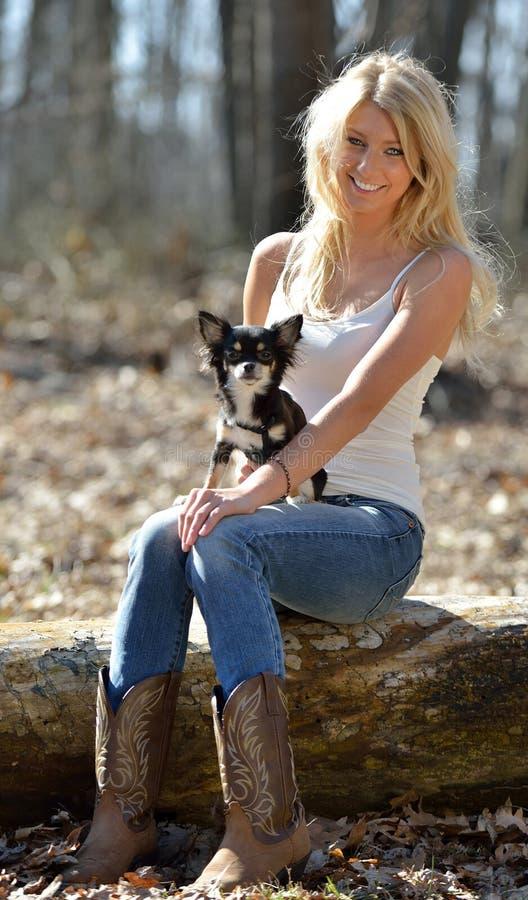 Retrato de uma mulher loura de sorriso bonita e de seu cão pequeno imagem de stock royalty free