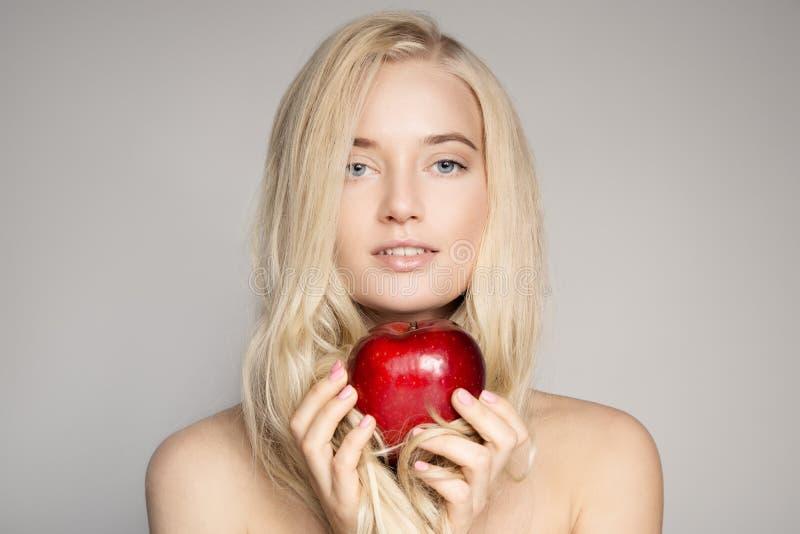 Retrato de uma mulher loura nova bonita com Apple vermelho fotografia de stock
