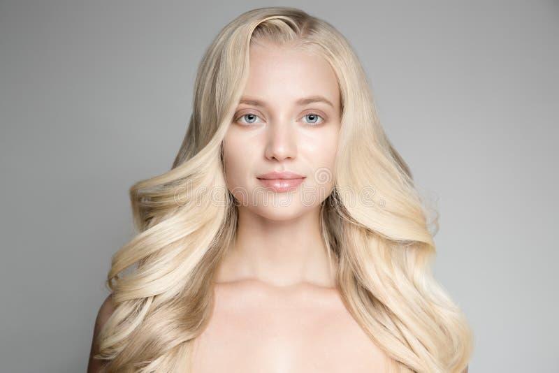 Retrato de uma mulher loura nova bonita com cabelo ondulado longo imagens de stock