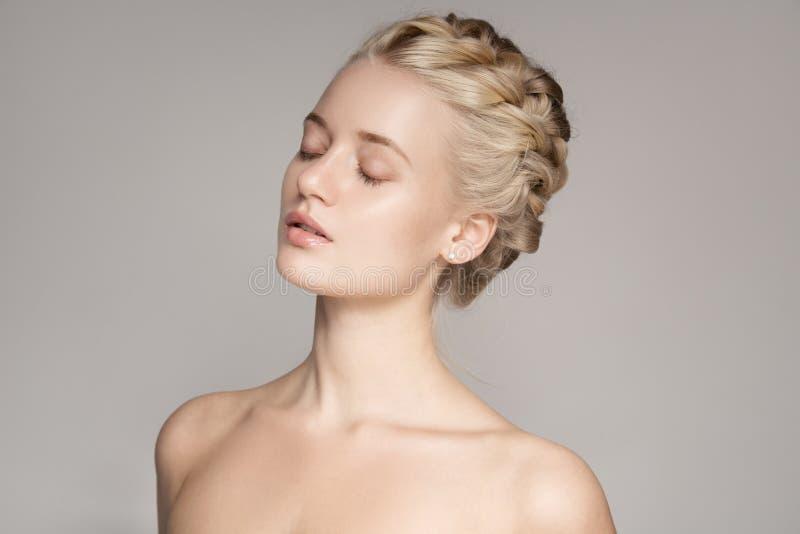 Retrato de uma mulher loura nova bonita com cabelos da coroa da trança fotos de stock royalty free