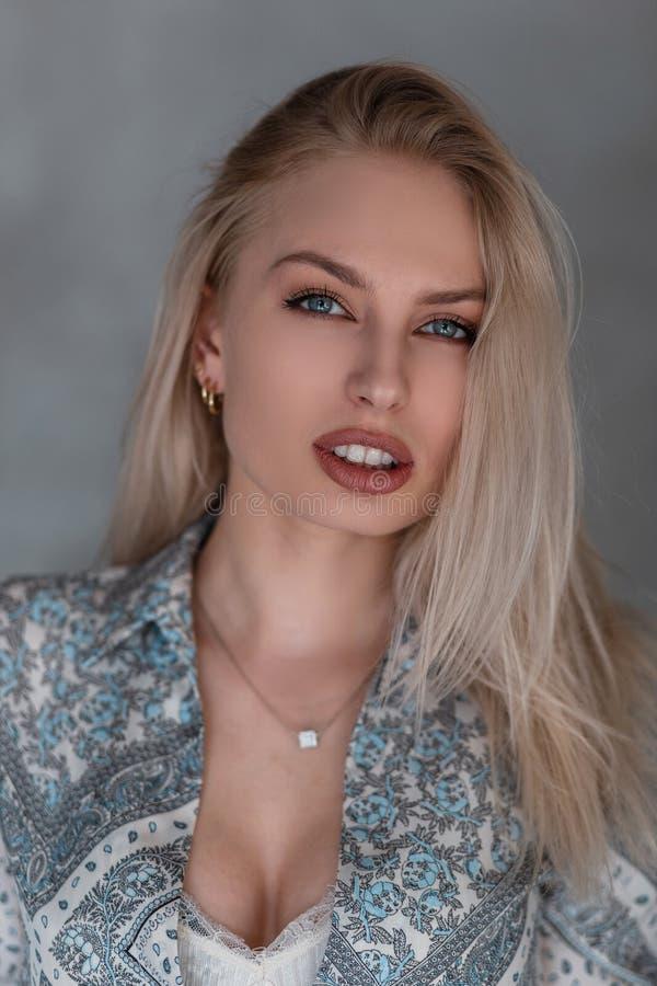 Retrato de uma mulher loura nova bonita com composição natural com olhos azuis com bordos 'sexy' em uma camisa do vintage com um  foto de stock royalty free