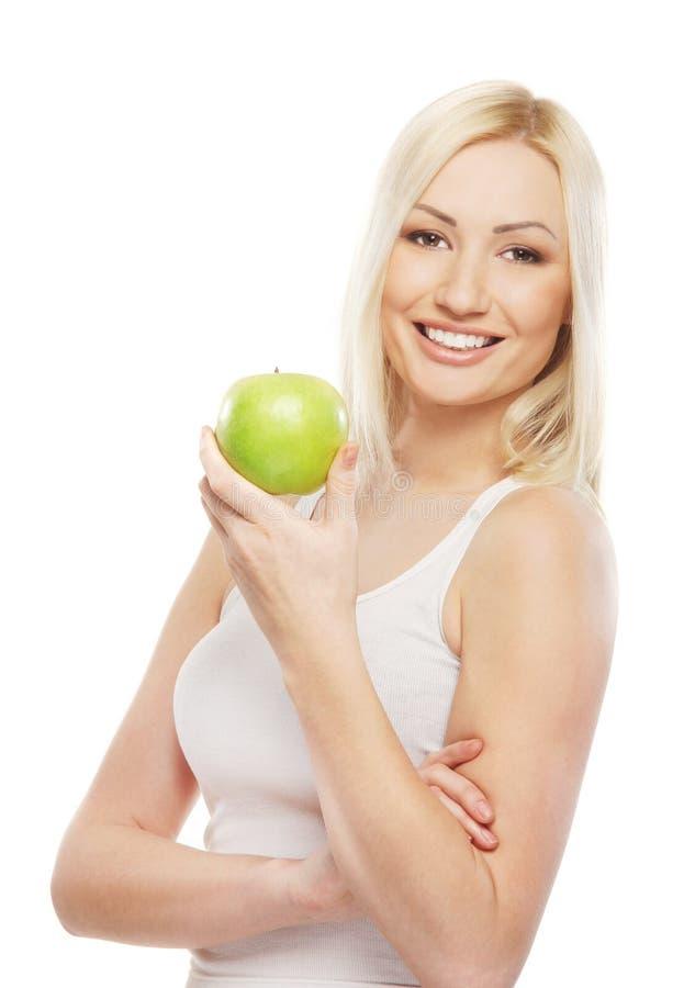 Retrato de uma mulher loura nova que prende uma maçã fotografia de stock royalty free