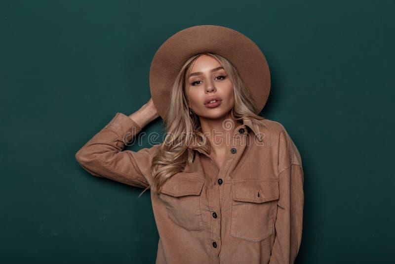 Retrato de uma mulher loura nova temporal com cabelo encaracolado em um chapéu elegante à moda com composição bonita natural imagem de stock