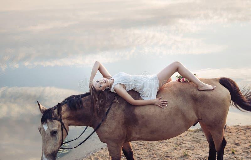 Retrato de uma mulher loura que encontra-se no cavalo imagens de stock royalty free