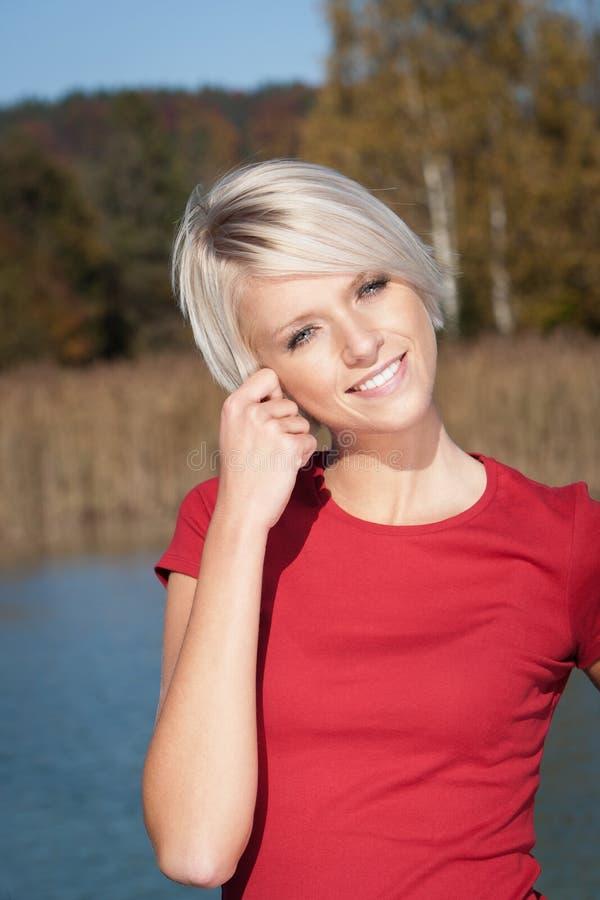 Retrato de uma mulher loura que toca na orelha imagem de stock royalty free