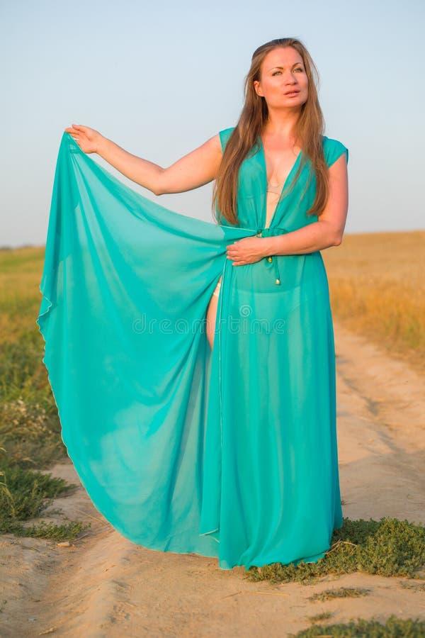 Retrato de uma mulher loura 'sexy' nova no vestido verde em um backgr imagens de stock