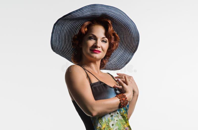 Retrato de uma mulher madura com cabelo vermelho e um chapéu imagem de stock