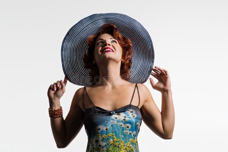 Retrato de uma mulher madura com cabelo vermelho e um chapéu fotografia de stock royalty free