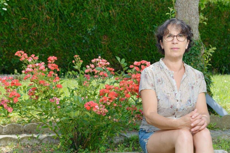 Retrato de uma mulher madura que senta-se no jardim foto de stock