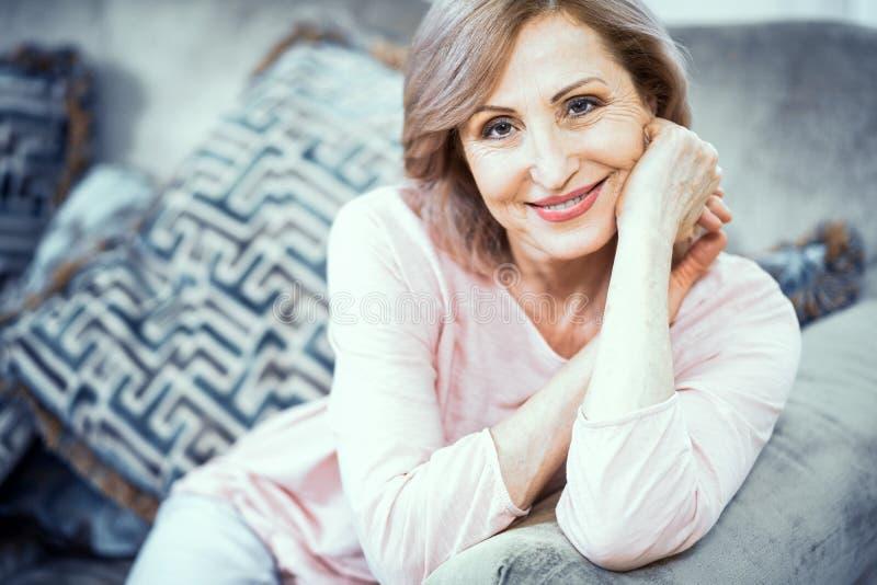 Retrato de uma mulher mais de 50 quem está descansando em casa na sala de visitas fotografia de stock royalty free