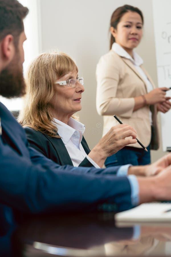 Retrato de uma mulher de meia idade durante a reunião de negócios imagens de stock royalty free