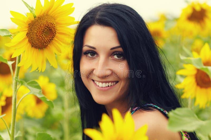 Retrato de uma mulher morena atraente num campo de girassóis fotografia de stock